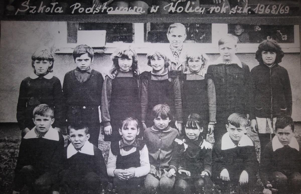 Klasa na tle szkoły z panią Piszczek. Autor zdjęcia nieznany.