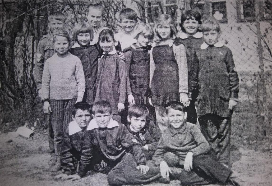 Zdjęcie uczniów z nauczycielką na tle szkoły z widocznymi krzewami. Autor zdjęcia nieznany.